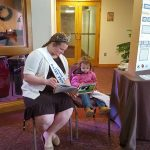 Lebanon County Dairy Princess Millena Bashore reads a book to Makenna Spangler.
